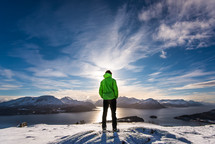 man standing on a snowy mountain looking out at a lake