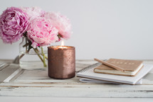 peonies, votive candle, and journals on a table