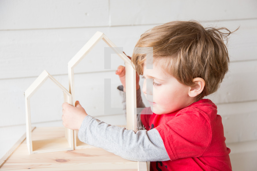 a child playing with wooden house shaped blocks