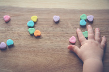 a toddler's hand touching heart shaped candy