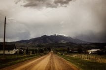 dirt road leading to a snow capped mountain peak