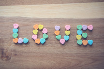 heart shaped candy in the shape of the word love on wood