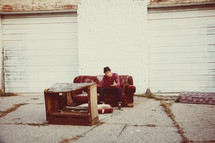 man sitting on a old couch in front of an old entertainment center outdoors