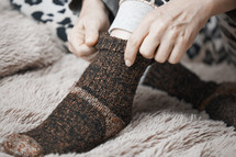 a woman putting on warm cozy socks