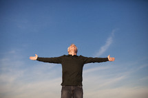 elderly man standing outdoors with his arms outstretched in worship to God