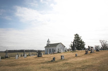 an old church surrounded by a cemetery