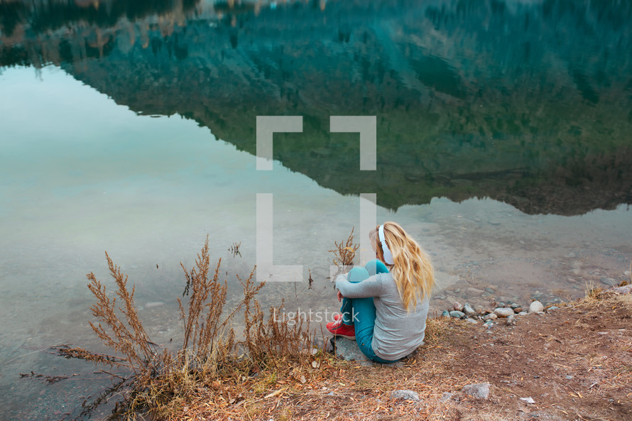 girl listening to headphones sitting by the edge of a pond