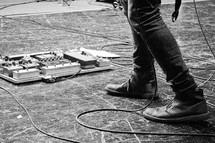 A man' foot near guitar pedals.