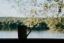 A coffee cup is silhouetted in front of a lake in northern Ontario. A peaceful moment for prayers and meditation.