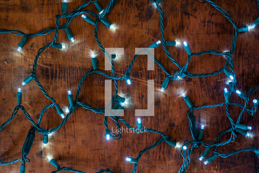 glowing string of Christmas lights on a wooden background