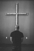 man standing in prayer in front of a cross