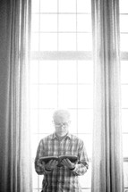 elderly man standing in a window reading a Bible