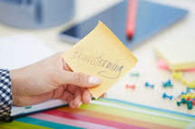a woman holding a sticky note with the words brainstorming