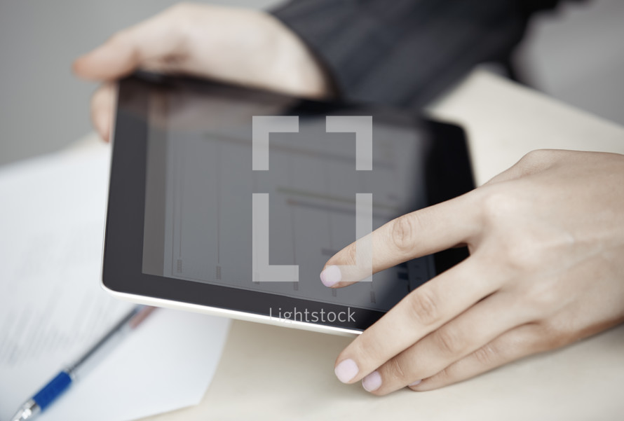 woman looking a charts on a tablet