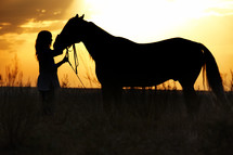 a woman and her horse at sunset