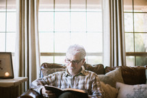 elderly man sitting on a couch reading a Bible