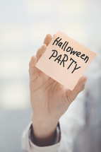 a woman holding a sticky note with the words Halloween Party