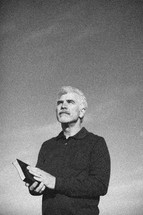 elderly man holding a Bible outdoors