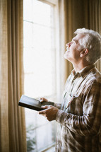 Man looking out window with Bible in his hands.