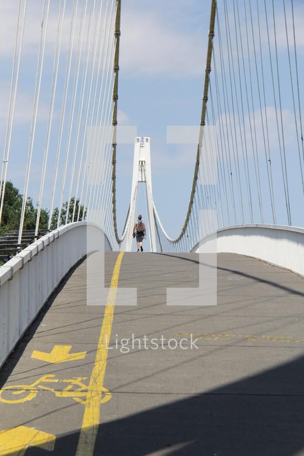a man walking across a bridge