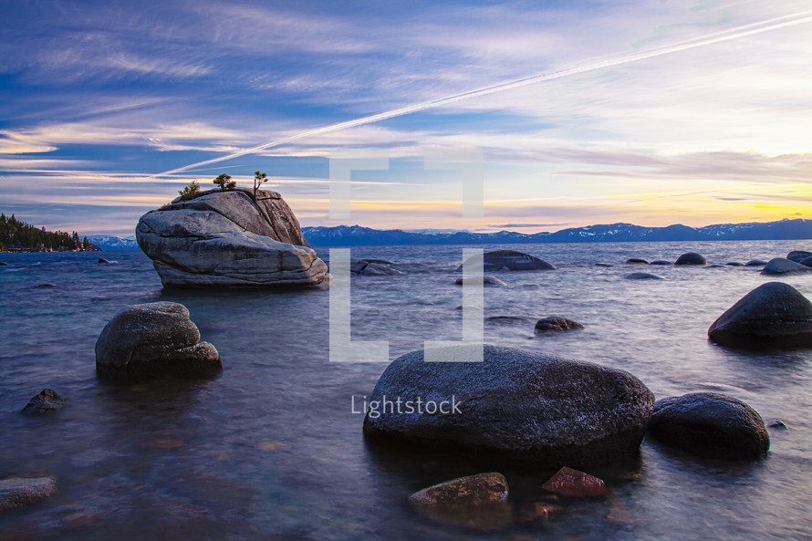 smooth rocks in shallow water along a shore