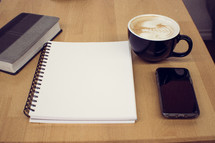 Bible, notebook, cellphone, and coffee cup on a wood table