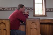 a man praying alone in church pews
