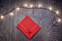 string of lights and red gift on a wood background