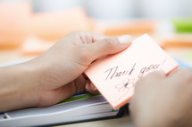 a woman holding a sticky note with the words thank you