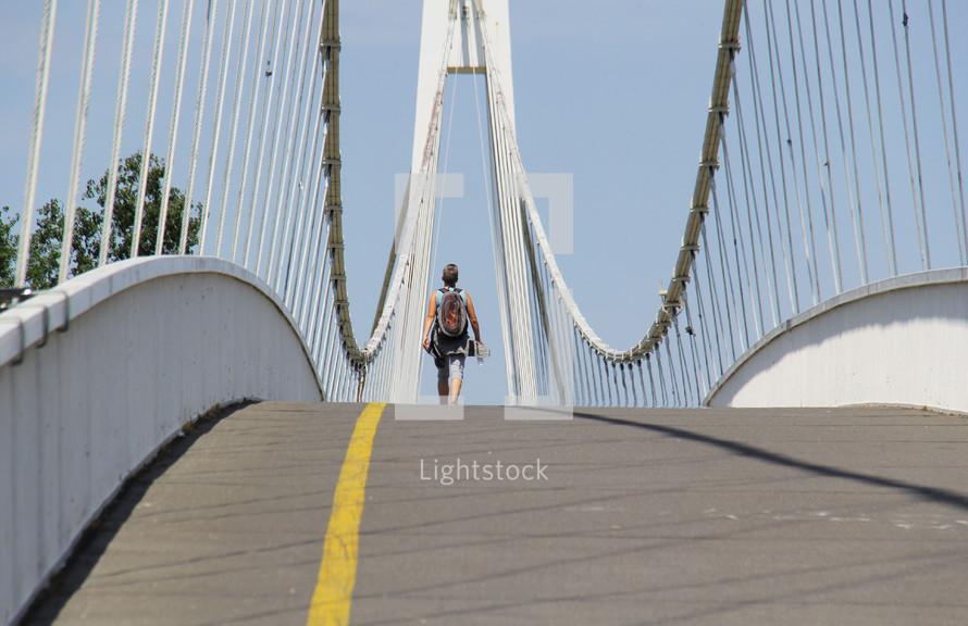 a man crossing a sloping bridge