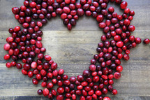 Cranberries in the shape of a heart on a wooden background