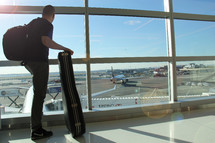 Man holding a guitar case looking out a window at an airport