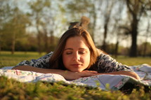 a woman lying on a blanket enjoying the warmth of the sun