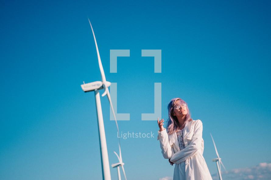 woman standing beside wind turbines