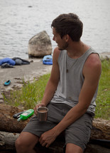 a man camping drink coffee by a river outdoors