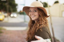 a young woman in a hat, gesturing to come this way