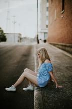 teen girl sitting on a curb