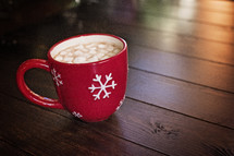 marshmallows and hot cocoa in a red mug on a wood floor
