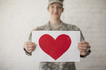 Red heart on white paper being held by an army soldier.