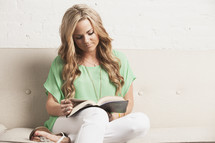 blonde woman sitting on a white couch reading a Bible