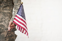 A soldier holds an American flag.