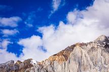 clouds in a blue sky over mountain peak