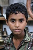 stoic face of a Bangladeshi boy