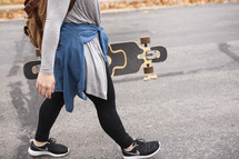 teen girl walking with a skateboard