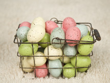 speckled eggs in a wire basket