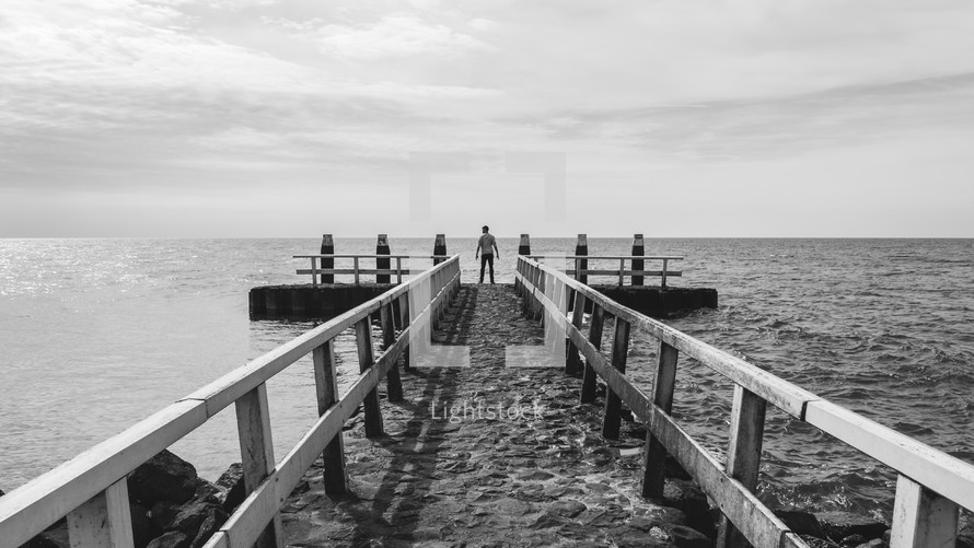 man standing at the end of a pier