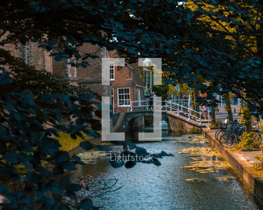 a couple kissing on a bridge