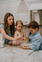 a mother baking cookies with her son and daughter