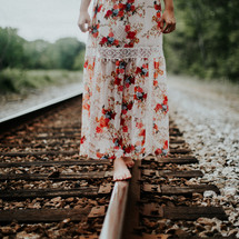 young woman balancing on train tracks