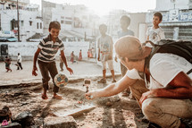 man filming children playing soccer in the dirt